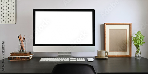 Workspace blank screen computer monitor putting on white working desk together with office stuff over living room orderly white wall as background Fototapet