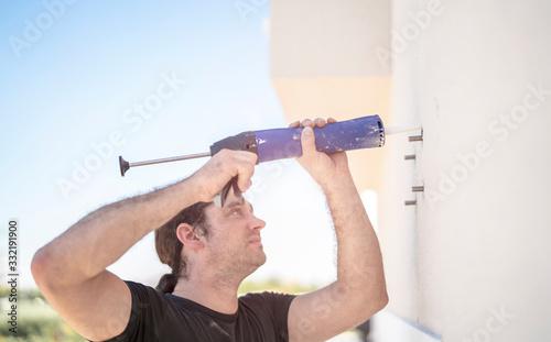 Handwerker klebt spezielle Gewindestangen ein, um später  eine Markise daran zu Wallpaper Mural
