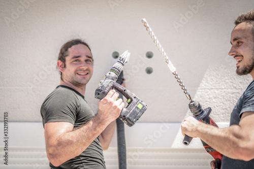 Photo zwei freundliche Handwerker bohren mit der Bohrmaschine in die Hauswand um späte