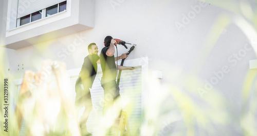 zwei freundliche Handwerker bohren mit der Bohrmaschine in die Hauswand um späte Canvas Print