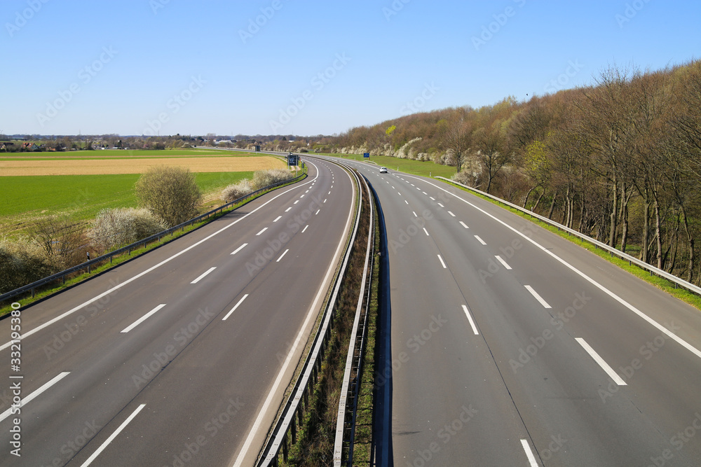Fototapeta Corona virus crisis stay at home and curfew concept: no traffic on deserted empty german highway A61 between Germany and Netherlands