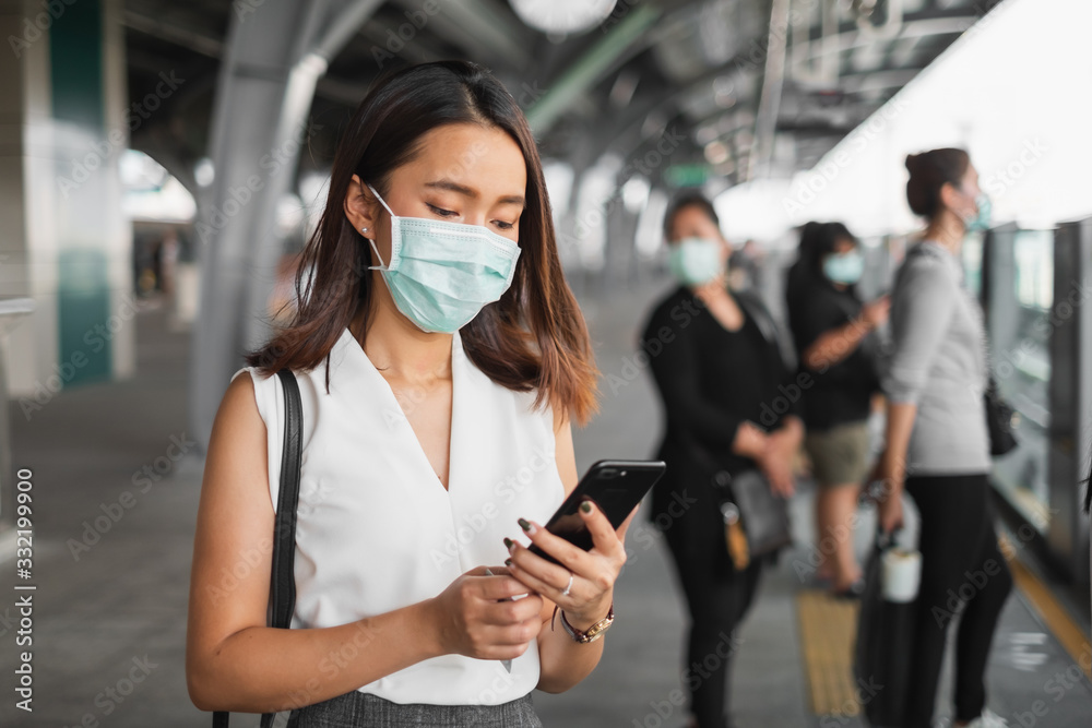 Fototapeta Coronavirus(Covid-19) concept, Asian woman wearing protective face mask to protect infection from coronavirus covid-19 standing at sky train and crowd people