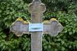 Steinkreuz mit Mundschutz auf einem alten Friedhof