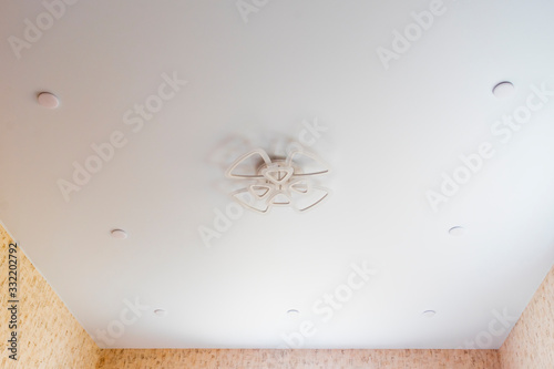 stretch ceiling in white. A decorative chandelier hangs in the center