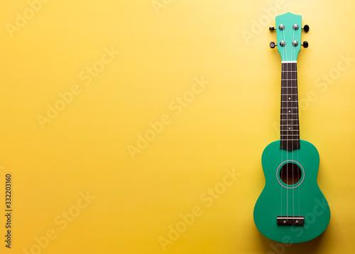 Fototapeta Green ukulele on a yellow background. Little Ukulele.  obraz