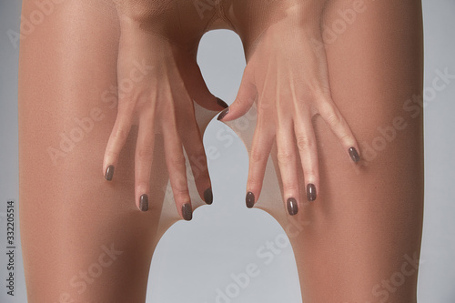 Part of woman body perfect shape hips legs skin tan wear stockings, nylons, pantyhose lingerie hosiery hose studio shot on white background.