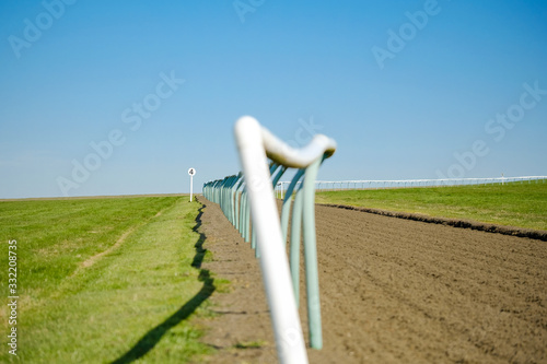 Shallow focus of a race horse trackside fencing seen adjacent to the soft textured race course surface Wallpaper Mural