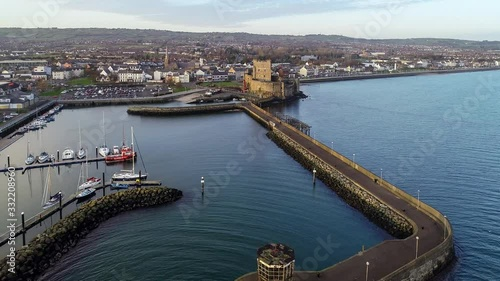 Medieval Norman Castle and harbor in Carrickfergus near Belfast in sunset light. Aerial 4K approaching video with marina, boat ramp, breakwater, yachts and town