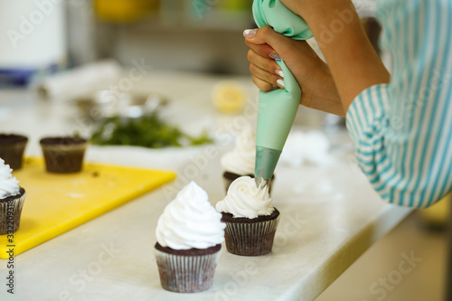 Photo The process of decorating chocolate cupcakes with airy protein cream