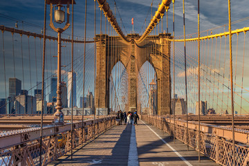 Brooklyn bridge daylight view with people walking, the american flag at its top and skylines in the background