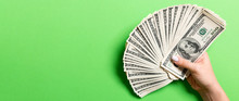 Top View Of Female Hand Holding A Fan Of One Hundred Dollars On Colorful Background. Loan Concept. Prosperity Concept With Copy Space