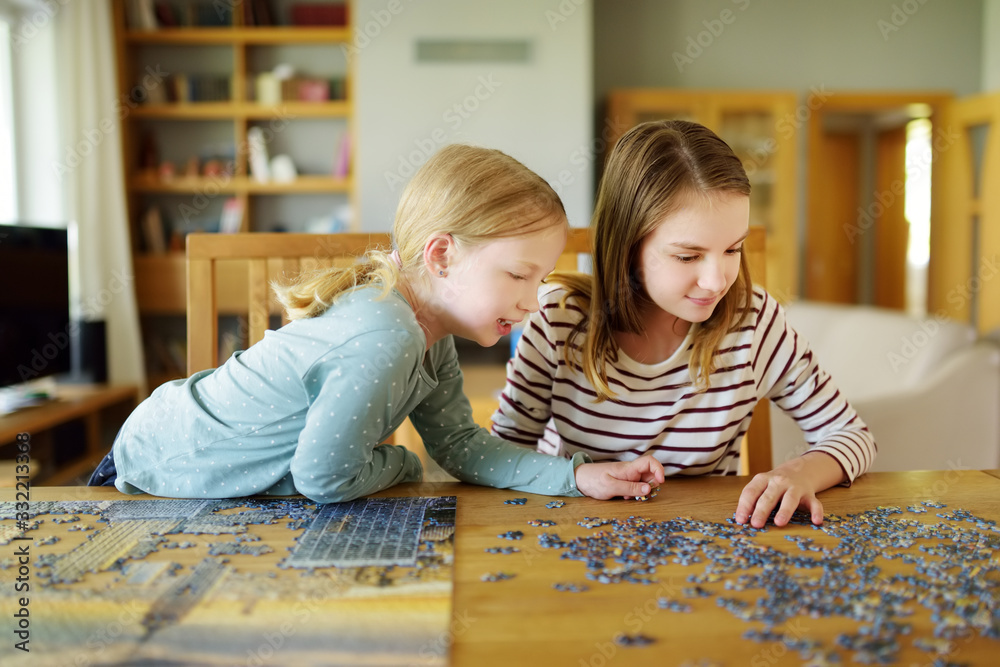 Fototapeta Cute young girls playing puzzles at home. Children connecting jigsaw puzzle pieces in a living room table. Kids assembling a jigsaw puzzle. Fun family leisure.