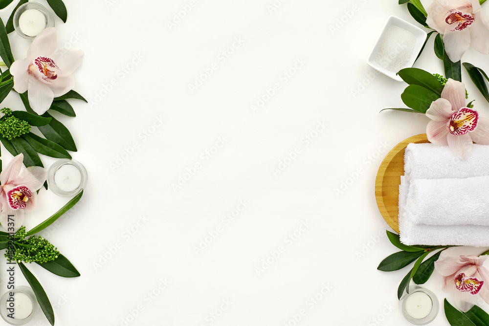 Fototapeta wellness and spa composition with towels, candle, tropical leaves and orchid flowers on white background. top view. copy space