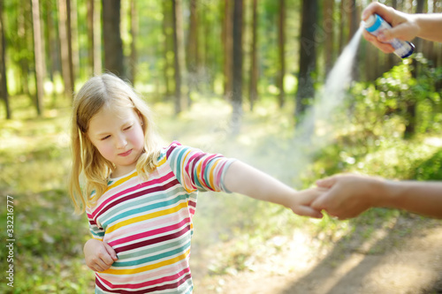 Fotografija Mother applying insect repellent to her daughter before forest hike summer day