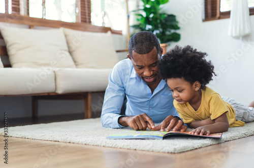 Happy African American father and son are reading a book and smiling while lying on floor spending time together at home. Children education and development concept.