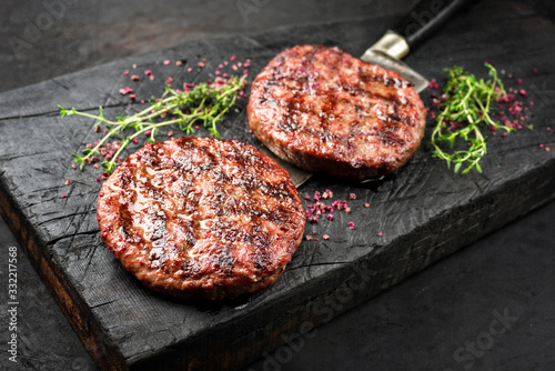 Barbecue Wagyu Hamburger with red wine salt and herbs as closeup on a charred wo Fototapeta