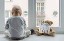 Toddler Sitting Next To Teddy Bear With Stay Home Sign