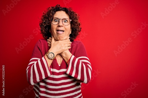 Middle age beautiful curly hair woman wearing casual striped sweater over red background shouting and suffocate because painful strangle Wallpaper Mural