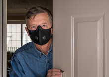 Senior Man With Face Mask Looking Worried At Front Door In Case Visitors Bring Coronavirus To His Home