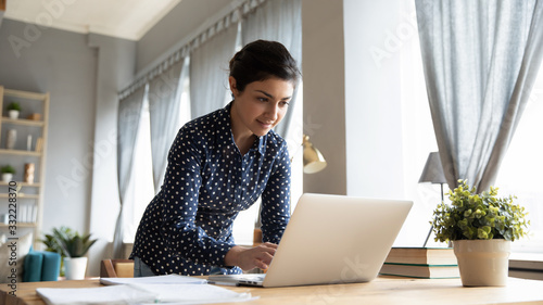 Obraz Smiling Indian girl standing at desk, working on laptop, looking at screen, browsing, searching information in internet, young female student studying online at home, chatting in social network - fototapety do salonu
