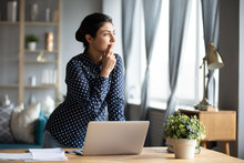 Thoughtful Indian Woman Standing At Desk, Businesswoman Freelancer Pondering Difficult Task, Looking Out Window, Touching Chin, Pensive Young Female Student Working On Research Project