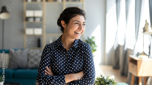 Fototapeta Head shot smiling Indian woman with arms crossed dreaming about good future, laughing young female standing at home, looking to aside at window, visualizing, thinking about new opportunity obraz