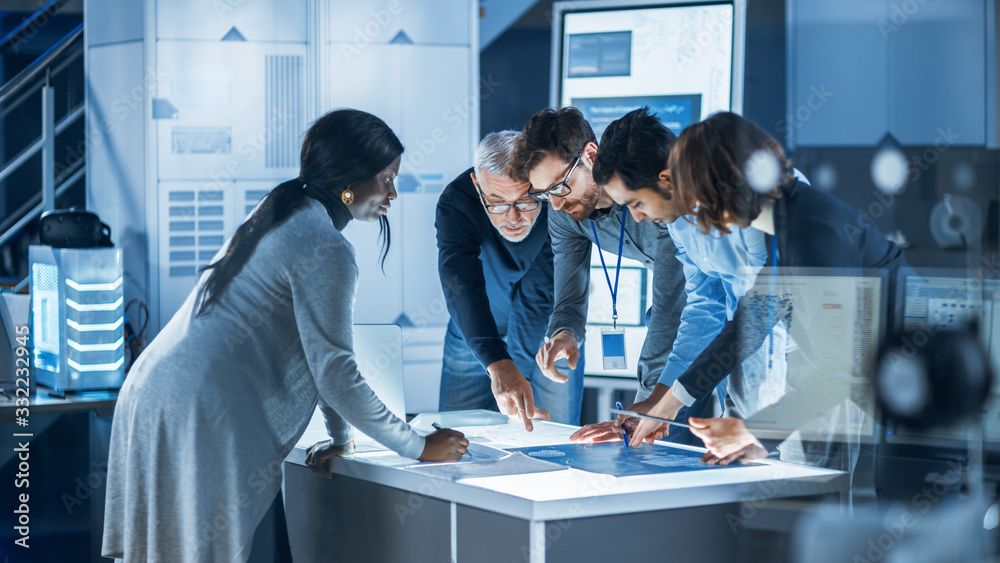 Fototapeta Engineers Meeting in Technology Research Laboratory: Engineers, Scientists and Developers Gathered Around Illuminated Conference Table Talking and Finding Solution, Inspecting Industrial Engine Design