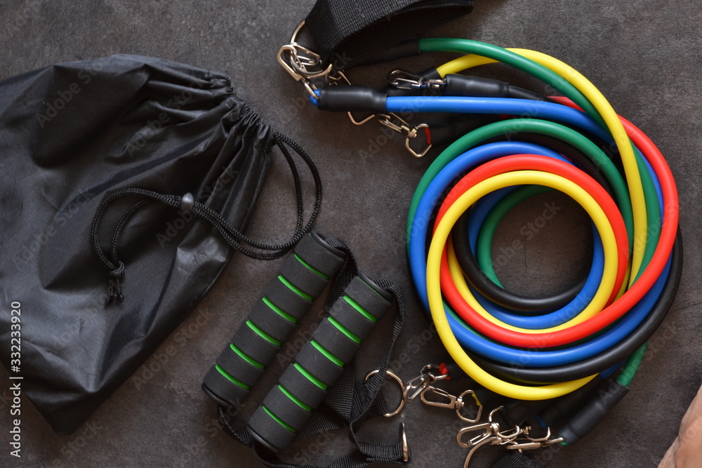 Fototapeta Sports accessory - expander with a carbine on a dark background.