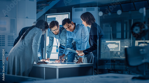 Fototapeta Engineers Meeting in Technology Research Laboratory: Engineers, Scientists and Developers Gathered Around Illuminated Conference Table, Talking and Finding Solution. Industrial Design Facility obraz