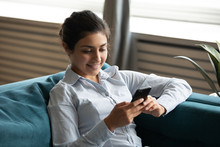 Smiling Indian Young Woman Using Smartphone, Sitting On Cozy Couch At Home, Satisfied Happy Girl Holding Phone, Looking At Screen, Chatting In Social Network, Surfing Internet, Spending Leisure Time
