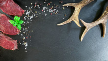 Roe Deer Steak With Basil, Pepper And Salt On The Dark Background.  In The Corner Is Roe Antlers As A Decoration.