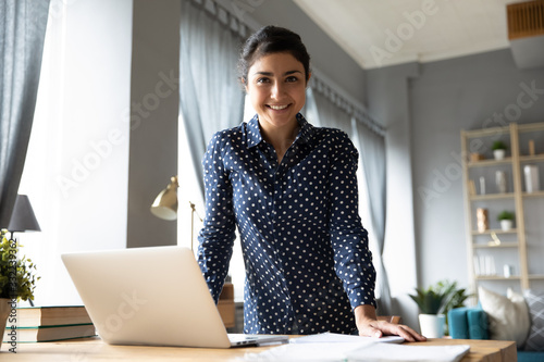 Fototapeta Portrait smiling Indian girl standing at desk with laptop, looking at camera, successful businesswoman freelancer posing for photo at workplace, satisfied excited female student in living room obraz