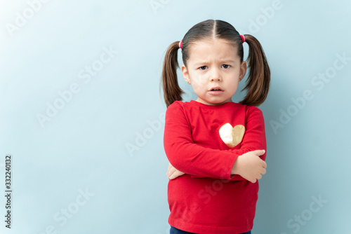 Caucasian little girl looking angry and serious with her arms crossed and frowni Canvas Print