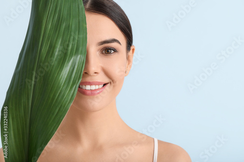 Valokuva Beautiful young woman with tropical leaf on color background
