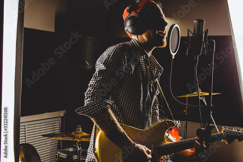 Photo young caucasian guitarist contemporaneously play guitar and sing a song in recording studio
