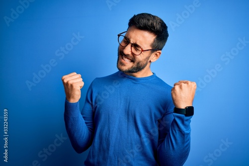 Foto Young handsome man with beard wearing casual sweater and glasses over blue background very happy and excited doing winner gesture with arms raised, smiling and screaming for success