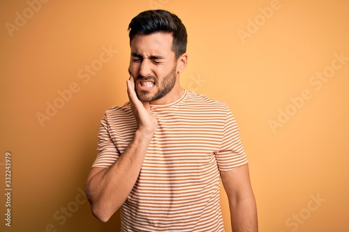 Fotografia Young handsome man with beard wearing casual striped t-shirt over yellow background touching mouth with hand with painful expression because of toothache or dental illness on teeth