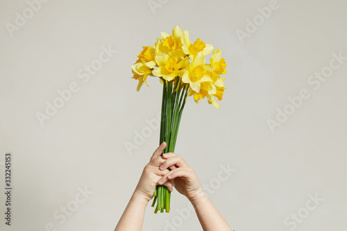 Fotografía A bouquet of yellow daffodils in kids hands on white background