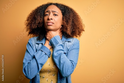 Young african american woman with afro hair wearing casual denim shirt over yellow background shouting and suffocate because painful strangle Wallpaper Mural