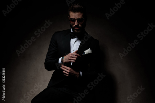 Photo businessman sitting and adjusting sleeve while looking at camera