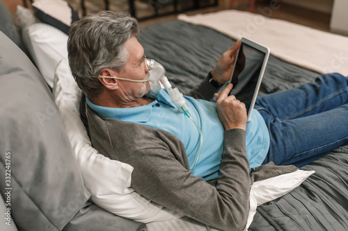 Man doing inhalation through oxygen mask at home bedroom and use his laptop Wallpaper Mural