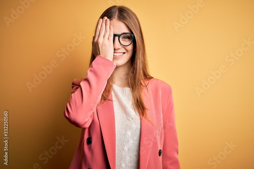 Photo Young beautiful redhead woman wearing jacket and glasses over isolated yellow background covering one eye with hand, confident smile on face and surprise emotion