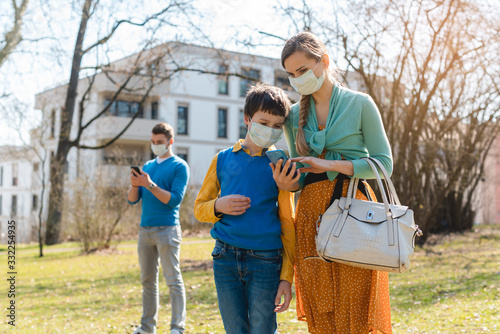 Obraz People during covid-19 crisis looking for news on their phones - fototapety do salonu