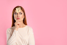 Pensive Woman With Question Mark Sticker On Forehead Against Pink Background. Space For Text