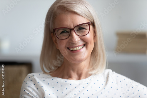 Fényképezés Close up head shot portrait of smiling attractive middle aged woman in eyeglasses