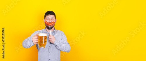 Valokuva man with glass of beer and grilled sausage on a fork in his hand, standing over