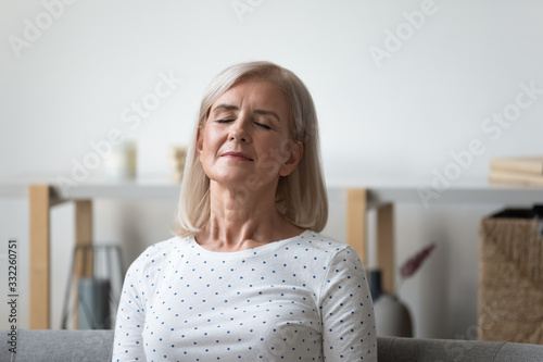 Fototapeta Peaceful middle aged blonde woman leaning on sofa, relaxing with closed eyes