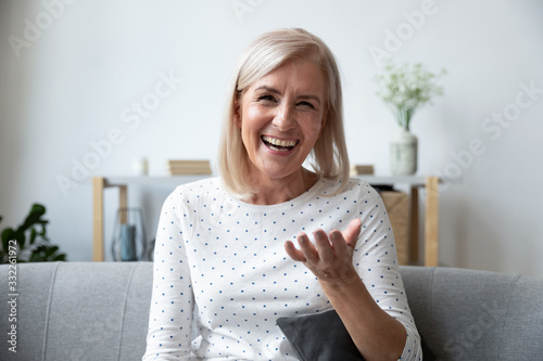 Cuadros en Lienzo Happy mature blonde lady sitting on couch, holding video call with friends, head shot close up portrait
