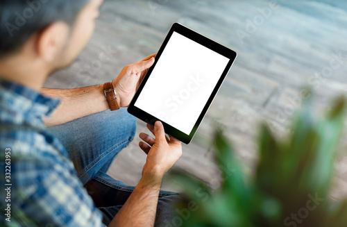 Obraz Mockup of a man holds tablet computer with isolated screen in his hands. View from above. Clipping path. - fototapety do salonu