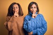 Middle age beautiful couple of sisters wearing casual sweater over isolated yellow background asking to be quiet with finger on lips. Silence and secret concept.